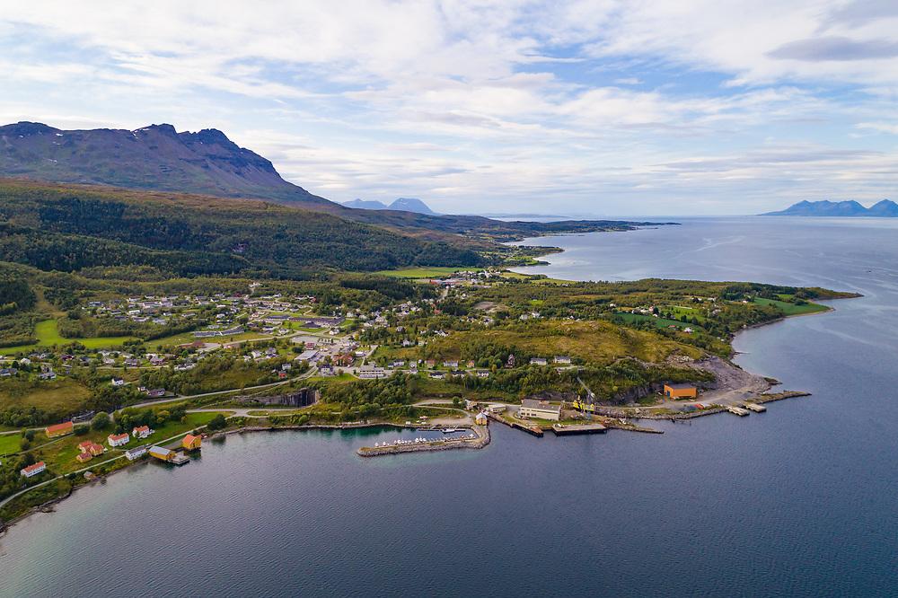 Dronefoto som viser oversiktsbilde over Hamnvik, Ibestad kommune i Sør-Troms, sett fra himmelen over havet.