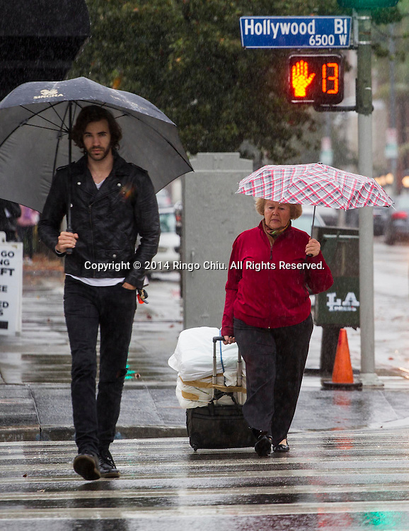 People carry umbrellas as they walk on the Hollywood Boulevard in Los Angeles, California, Tuesday, December 2, 2014. The rain, along with gusty winds, is the result of a Pacific storm system. Forecasters said the storm should drop about 1 to 2 inches of rain along the coast and in valley areas, and 2 to 5 inches in the mountains and foothills.(Photo by Ringo Chiu/PHOTOFORMULA.com)