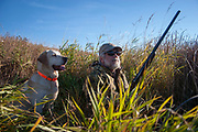 Experienced hunter John Davidson, duck hunting with his faithful labrador retriever Chester near Minot, North Dakota, United States. They wait patiently as ducks circle until they come into range. John has been shooting for most of his life and puts considerable efforts into his hunting, efforts which reward him with wild game meats. In this part of North Dakota, glacially formed flat land is filled with pock-marked shallow holes, which fill with eater making ideal sloughs for ducks such as Mallard, Widgeon and the more prized Canvas Back.