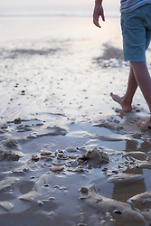Low section view of a girl walking on the beach, Lit-et-Mixe, France