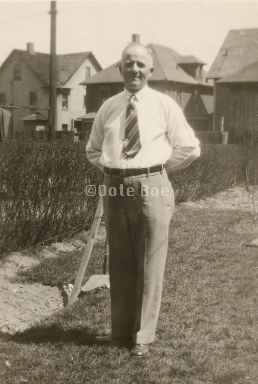 Elderly man standing in his backyard