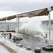 On a very windy day, waves crash into the wall on the Bosphorus Strait in Istanbul, Turkey.