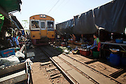 Mar. 24, 2009 -- The train from Baan Laem pulls into the market in Samut Sangkhram. The Mahachai Rail Line is a commuter line that runs from the Wong Wian Yai train station in the Thonburi section of Bangkok to the fishing port and market town of Samut Sakhon, which used to be known as Mahachai. An extension of the line runs from Baan Laem, near Samut Sakhon, to Samut Songkhram, another fishing port south of Samut Sakhon. Each stretch of the line takes about an hour.    Photo by Jack Kurtz