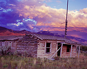 Abandoned log cabin in the Little Lost River Valley with the Lehmi Range beyond, Clyde, Idaho.