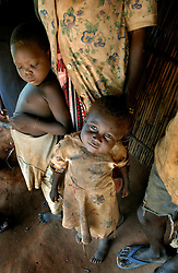 The children of Cosmos Mbawala, 55, Jumada, 5, left, and Salama, 3, sit outside their hut as their father talks about the attack of their brother Cosmos Chakoma, 12, who was killed by a lion in the village of Hingawali, Tanzania. Ami Vitale