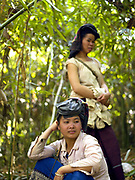 Two Tai Dam ethnic minority women take a break from collecting 'Nor Khom', bitter bamboo shoots in the forest, Ban Na Kham, Oudomxay province, Lao PDR. They are collecting them both for their own consumption and for selling at the small roadside market in the village of Ban Na Mor.