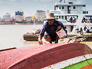 """17 JUNE 2013 - YANGON, MYANMAR:    A Burmese boat taxi operator paints his boat near the dock of the Yangon-Dala Ferry on the Dala side of the river. Yangon is in the background. The ferry to Dala opposite Yangon on the Yangon River is the main form of transportation across the river. Every day the ferry moves tens of thousands of people across the river. Many working class Burmese live in Dala and work in Yangon. The ferry is also popular with tourists who want to experience the """"real"""" Myanmar. The rides takes about 15 minutes. Burmese pay about the equivalent of .06¢ US for a ticket.  Foreigners pay about the equivalent of about $4.50 US for the same ticket.   PHOTO BY JACK KURTZ"""