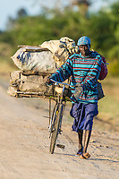 Mozambican transporting charcol to the market on his bicycle, Rio Savanne, Beira, Sofala Province, Mozambique