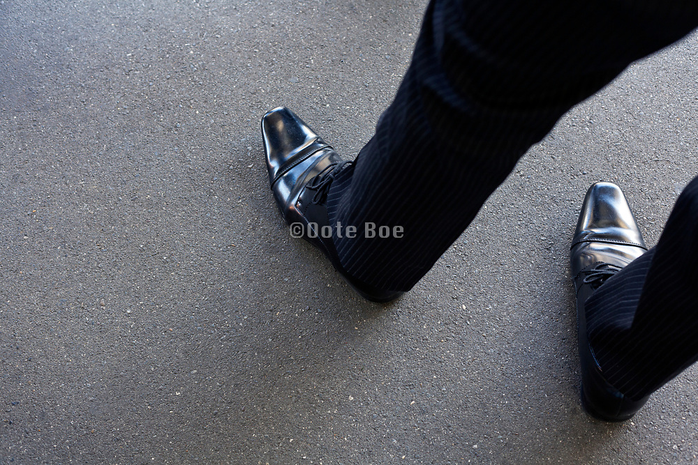 businessman wearing highly polished shiny black leather shoes