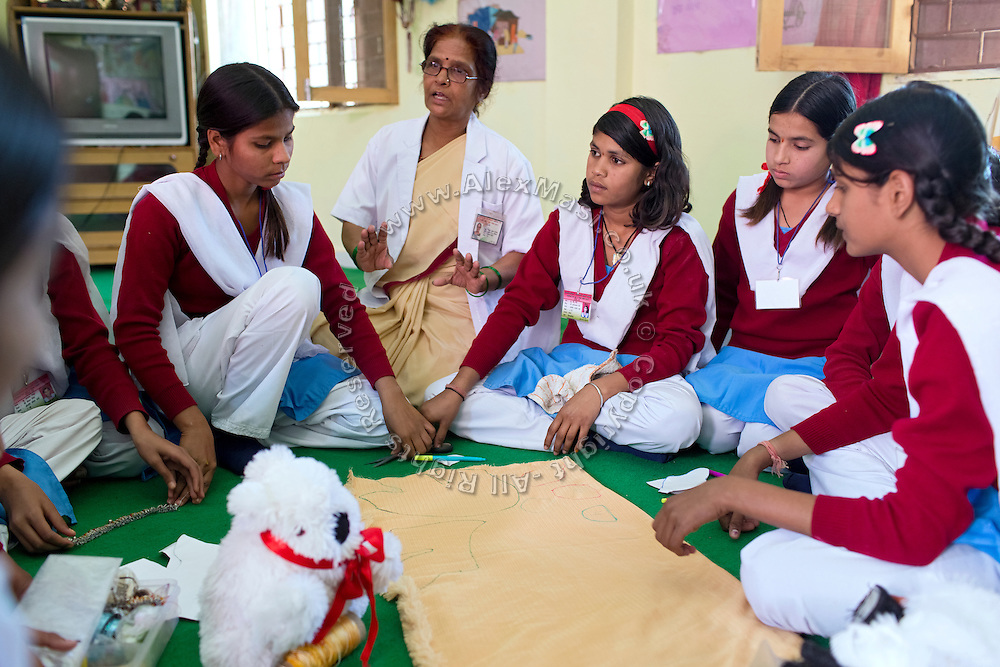 Ritu Gaur, 13, (centre right) is participating to a Skills Development class focusing on sawing, led by Sushila Chourasiya, 53, the assistant warden of the Jamoniya Tank Girls Hostel, near Sehore, Madhya Pradesh, India, where the Unicef India Sport For Development Project has started in 2012. Covering 313 state-run girls' hostels and 207 mixed hostels in Madhya Pradesh, the project ensures that children from Scheduled Tribes (ST) and others amongst the poorest people in India, can easily access education and be introduced to sports. Field workers from Unicef also oversee their nutrition and monitor the overall conditions of each pupil.