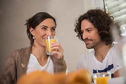 Mid adult woman drinking juice while her husband looking at her, Munich, Bavaria, Germany