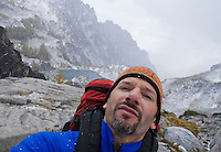 Self portrait of a man wearing a backpack in the mountains with snow falling, Enchantment Lakes Wilderness Area, Washington Cascades, USA.