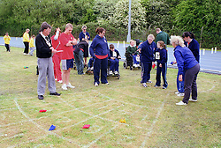 Coach and disabled children taking part in Mini games sports event held at Stoke Mandeville Stadium,