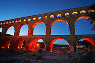 Picture at nightime of the ancient Roman Aqueduct of the Pont du Gard which crosses the River Gardon near Vers-Pon-du-Gard, France. Part of the 50 km long aqueduct that served the Roman town of Nemausus (Nimes) its 3 tiers of arches stand 48 m high (160 ft). A UNESCO World Heritage Site. .<br /> <br /> Visit our ROMAN ART & HISTORIC SITES PHOTO COLLECTIONS for more photos to download or buy as wall art prints https://funkystock.photoshelter.com/gallery-collection/The-Romans-Art-Artefacts-Antiquities-Historic-Sites-Pictures-Images/C0000r2uLJJo9_s0