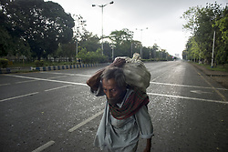 An old man carries goods on a deserted street in Kolkata during the 2nd phase of lockdown in India due to covid 19 pandemic. Kolkata, West Bengal, India, April 28, 2020. Arindam Mukherjee