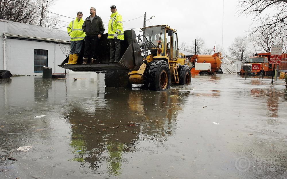 Workers at the Department of Public Works in Teaneck, New Jersey ride in bulldozer  while removing equipment from a flooded lot on Monday 16 April 2007. A large storm delivered records amount of rain to the East Coast of the United States over the weekend and today