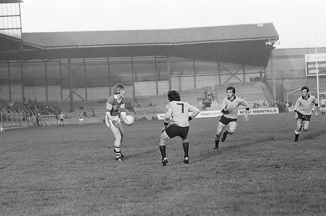 Kerry about the palm the ball up field away from the on coming Dublin Players during the All Ireland Senior Gaelic Football Semi Final, Dublin v Kerry in Croke Park on the 23rd of January 1977. Dublin 3-12 Kerry 1-13.