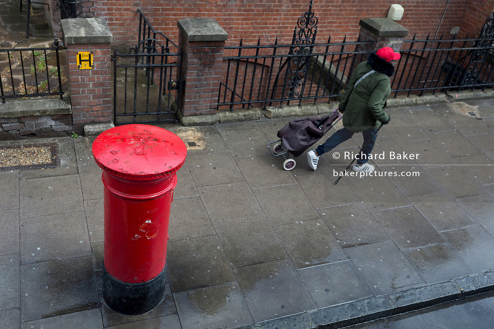 Looking down from the top of a London bus on to the top of a Royal Mail postal box as a lady wearing a red hat walks along the Walworth Road in Southwark, on 9th May 2019, in London, England.