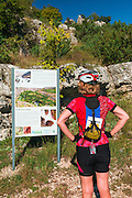 Visitor reading an Interpretive sign at Manojlovac Falls, Krka National Park, Dalmatia, Croatia