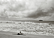 Nude woman laying on her back on beach with cloudy sky