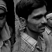Workers outside an auto parts plant in New Delhi, India that uses asbestos for manufacturing components for cars.  These workers wear no safety equipment at all while working and have no access to any equipment to prevent the inhalation of dust and asbestos.