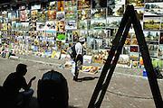 Krakau, Poland, Jul 15, 2005, A tourist looks at a wall of art at the Pijarka's art market.