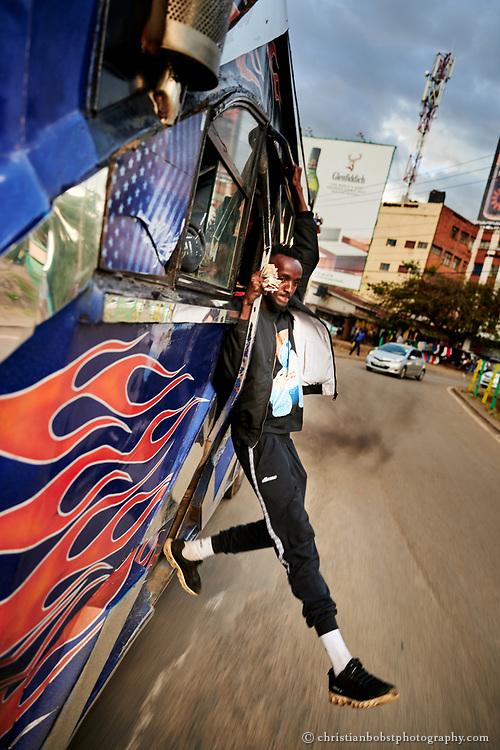Die Makangas lehnen sich wöhrend der Fahrt oft und gerne durch die offenen Türe der Matatus an die mehr oder weniger frische Luft. Die Unterhaltung der Fahrgäste durch gefährliche Stunts gehört dabei zum Standard-Repertoire vieler Makangas – auf spektakuläre Art demonstriert dies Bahati Kimathi (23), ein Makanga des Hot-Wheel-Matatus, welches zwischen Rongai und dem Zentrum Nairobis  verkehrt.