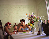 Laura Lulu (on left) recieves reading and writing school lessons from Rodica, her family maid, whilst her brother Ionut watches, in her home, in the village of Sintesti, in Romania, early August 2006. The Kalderari roma of Sintesti are by tradition metal workers, originally making alcohol stills, pots and pans, but now dealing in scrap metal. The large profits from their business have enabled them to build large houses in the village of Sintesti, 20km from Bucharest, and to invest in fast, Western brand name cars such as BMW's, Mercedes and Porsche.