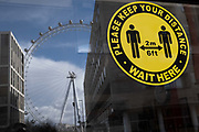 A yellow and black sticker which urges social distancing to customers, faces the street from inside a closed retailers window in Waterloo, where the London Eye still revolves while empty during the third lockdown of the Coronavirus pandemic, on 11th March 2021, in London, England.