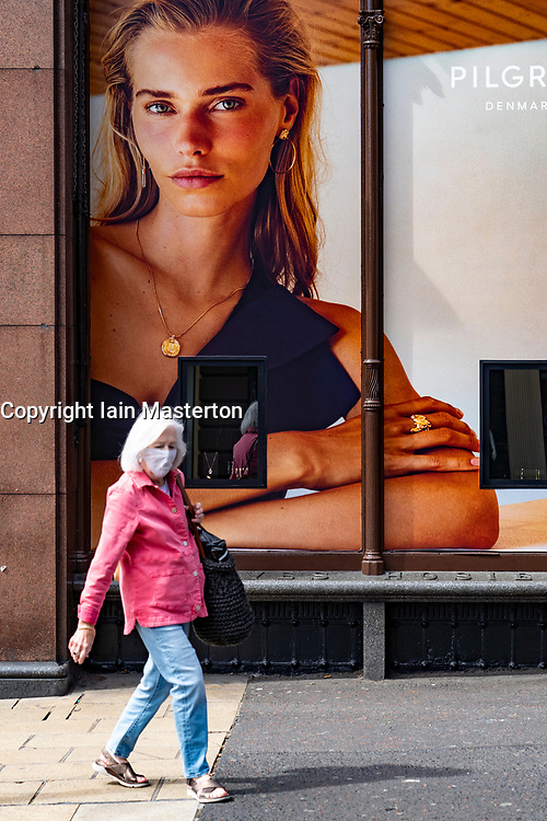Edinburgh, Scotland, UK. 28 July, 2020. Business and tourism slowly returning to the shops and streets of Edinburgh city centre. Woman walks past shop window advertising display in Jenners department store. The retail industry is suffering severe problems with many job losses. Iain Masterton/Alamy Live News