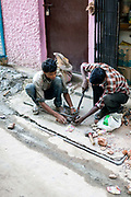 Two men plumb in and cement illegal water pipes in the Munika area. New Delhi, India