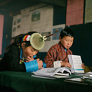 """Every other day, Layap girl are asked to wear the traditional Layap outfit, including the conical bamboo hat. On other days, they must wear the """"kira"""" the national dress. Visiting the only school in Laya village."""