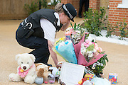 © Licensed to London News Pictures. 23/04/2014. New Malden, UK.  A police officers straightens flowers left at the scene.  The scene in New Malden where a woman has been arrested after the discovery of three bodies of children in a house overnight. Photo credit : Stephen Simpson/LNP