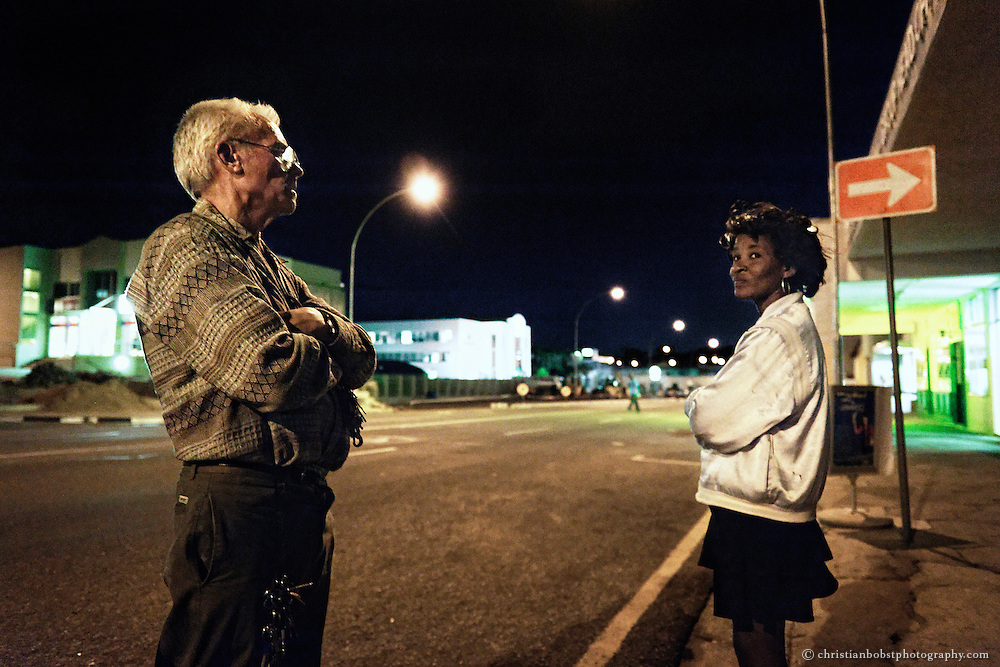 """(2008) Father Hermann talks to a streetwalker who is looking for clients at the Ausspannplatz, a street-walkers patch in the city center of Windhoeck. This area is not safe for the women, especially not at nighttime. Sex workers can´t expect any protection from the police, because prostitution is illegal in Namibia. """"When it's dark the ladies are wanted by many people, but during the day in parliament they want to burn them out."""" says Hermann in an interview with a local newspaper."""