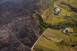 © Licensed to London News Pictures . 04/07/2018 . Bolton , UK . Free to use aerial photograph provided by the Woodland Trust showing the scarred landscape at Winter Hill , as fire-fighters continue to work to control the spread of the blaze . The Woodland Trust estimates it has lost a fifth of the area it manages around Winter Hill , damaging precious moors and upland grassland , endangering the surrounding woods and wildlife and threatening people's homes . Photo credit: Joel Goodman/LNP