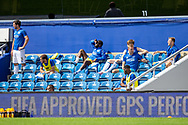 Queens Park Rangers substitutes in the lower tier of the South Africa Road Stand during the EFL Sky Bet Championship match between Queens Park Rangers and Barnsley at the Kiyan Prince Foundation Stadium, London, England on 20 June 2020.