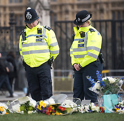 © Licensed to London News Pictures. 22/03/2018. London, UK. Police officers look at flowers left on Parliament Square, outside the Houses of Parliament in Westminster, London on the one year anniversary of the the Westminster Bridge Terror attack. A lone terrorist killed 5 people and injured several more, in an attack using a car and a knife. The attacker, 52-year-old Briton Khalid Masood, managed to gain entry to the grounds of the Houses of Parliament and killed police officer Keith Palmer. Photo credit: Ben Cawthra/LNP