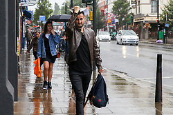 © Licensed to London News Pictures. 10/08/2019. London, UK. A man shelters from the rain underneath papers during a downpour on Green Lanes, Harringay in north London. Photo credit: Dinendra Haria/LNP