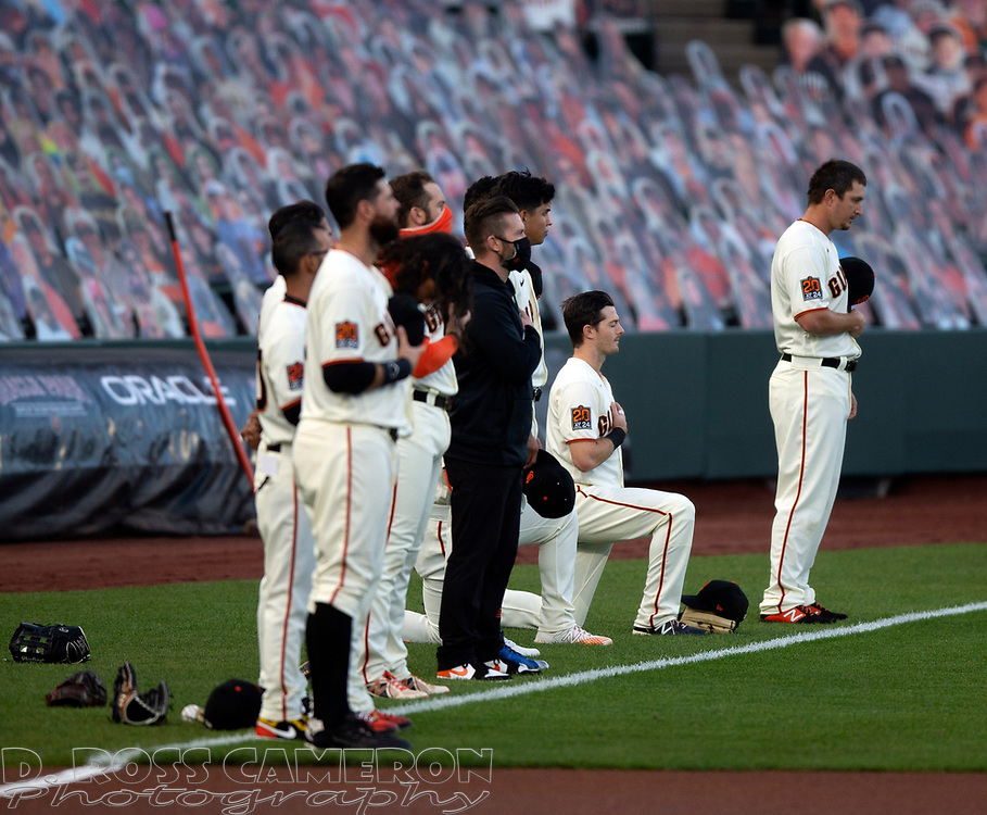 Sep 16, 2020; San Francisco, CA, USA; San Francisco Giants Mike Yastrzemski, second from right, takes a knee during the playing of the national anthem before a baseball game against the Seattle Mariners at Oracle Park. Mandatory Credit: D. Ross Cameron-USA TODAY Sports
