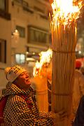 Man looking up at burning straw at night, Nozawaonsen, Japan
