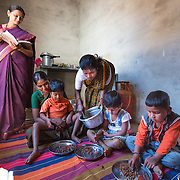 CAPTION: Anaganwadi (pre-school) Supervisor Jayalakshmi observes anganwadi feeding. Under the Chamkol programme, anganwadi workers will soon start receiving focussed training on ways to minimise the risk of disability during pregnancy, childbirth or infancy, on how to identify and respond to suspected impairments and how to care for, nurture and support children with different impairments. LOCATION: Mallianpura (village), Kasaba (hobli), Chamrajnagar (district), Karnataka (state), India. INDIVIDUAL(S) PHOTOGRAPHED: From left to right: Jayalakshmi, Nagamma H.S., Aishwarya, Mahadevamma, Bhavani and Mahadevprasad.