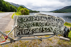 Glen Coe, Scotland, UK. 4 July, 2020. Tourists travel to Glen Coe on first weekend after 5 mile travel restriction was lifted by the Scottish Government. Pictured; Sign at Ballachulish warning that Covid-19 virus has not gone away and to obey Scottish Government rules.  Iain Masterton/Alamy Live News