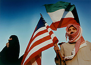 Kuwaiti holding stars and stripes celebrates in front of the U.S. Embassy in Kuwait City, the day after the city was liberated from the Iraqis by U.S. forces.