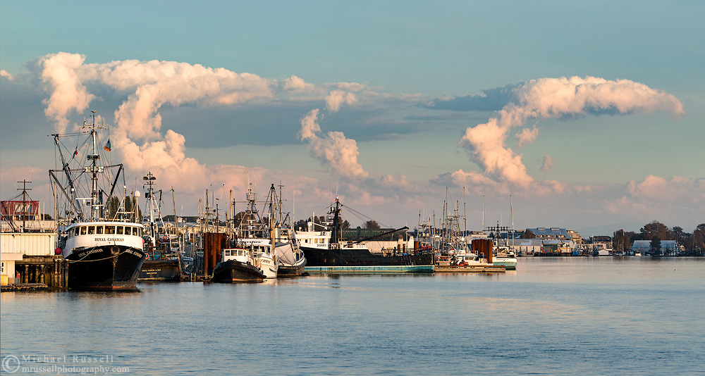 Towering Cumulus clouds drift across the evening sky over fishing boats in Steveston Harbour.  Photographed from Garry Point Park in Richmond, British Columbia, Canada.