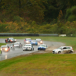 Cars spin into the exit of Turn 1 during the Grand-Am Continental Tire Sports Car Challenge ST race at Lime Rock Park in Lakeville, Conn.