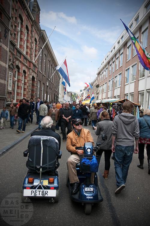 Twee mannen in een scootmobiel tijdens bevrijdingsdag in Roermond