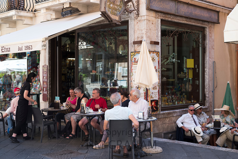 Cafe culture - people sitting at pavement cafeteria in Corso Umberto I in the city of Taormina, East Sicily, Italy