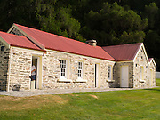 A tourist (woman) explores the historic Skipper's Point School, near Queenstown, Otago, New Zealand.