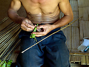 Tan, a Tai Lue ethnic minority man prepares his rods for fishing in the river nearby Ban Bo Ha village, Luang Prabang province, Lao PDR. For families living away from the main roads and markets, food caught or collected from the wild, especially edible plants and small animals still make up fifty per cent of their diet.  Nature's bounty in providing for the Lao may be plentiful, but this does not mean that the task of growing and finding enough food for family subsistence and maintenance is easy. It is a major preoccupation of rural families and takes the bulk of time and energy of every man, woman and child.
