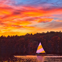 New England sunset featuring a sailboat sailing in peace and quietude across Lake Cochituate at Cochituate State Park in Natick, Massachusetts. <br />